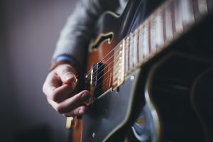 Hands playing a guitar