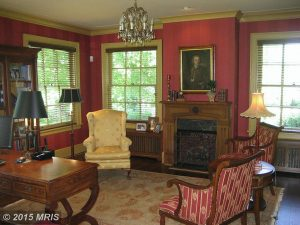 living room of a house furnished with chairs and a painting