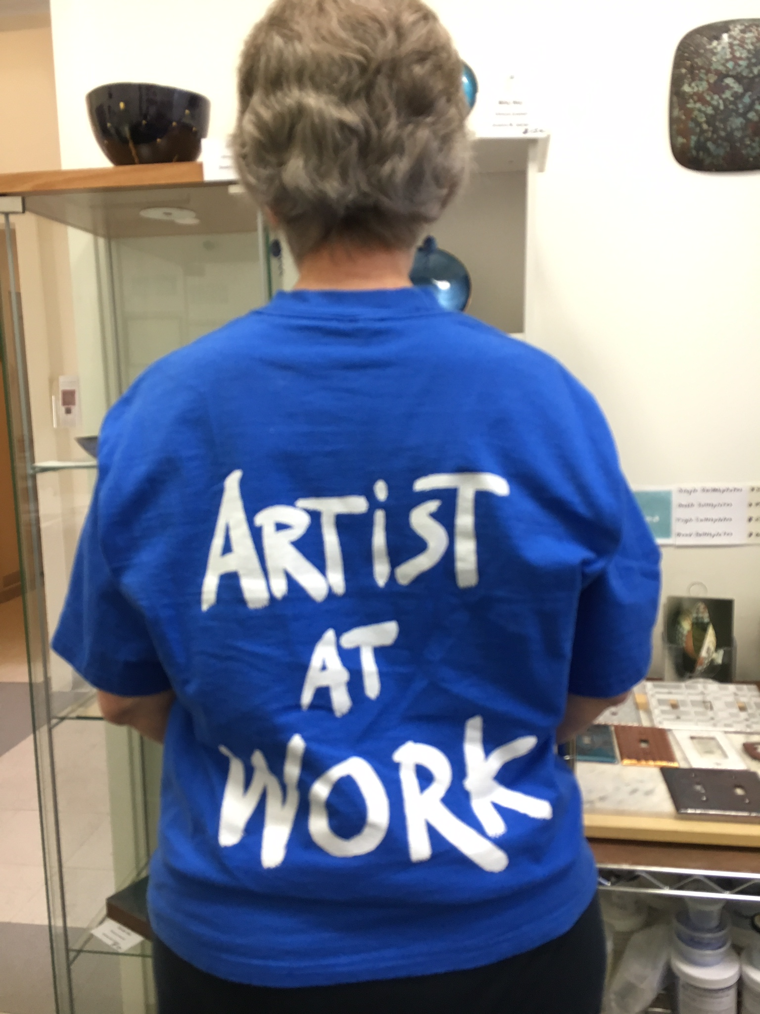 woman standing by pottery wearing a shirt with the words artist at work on it