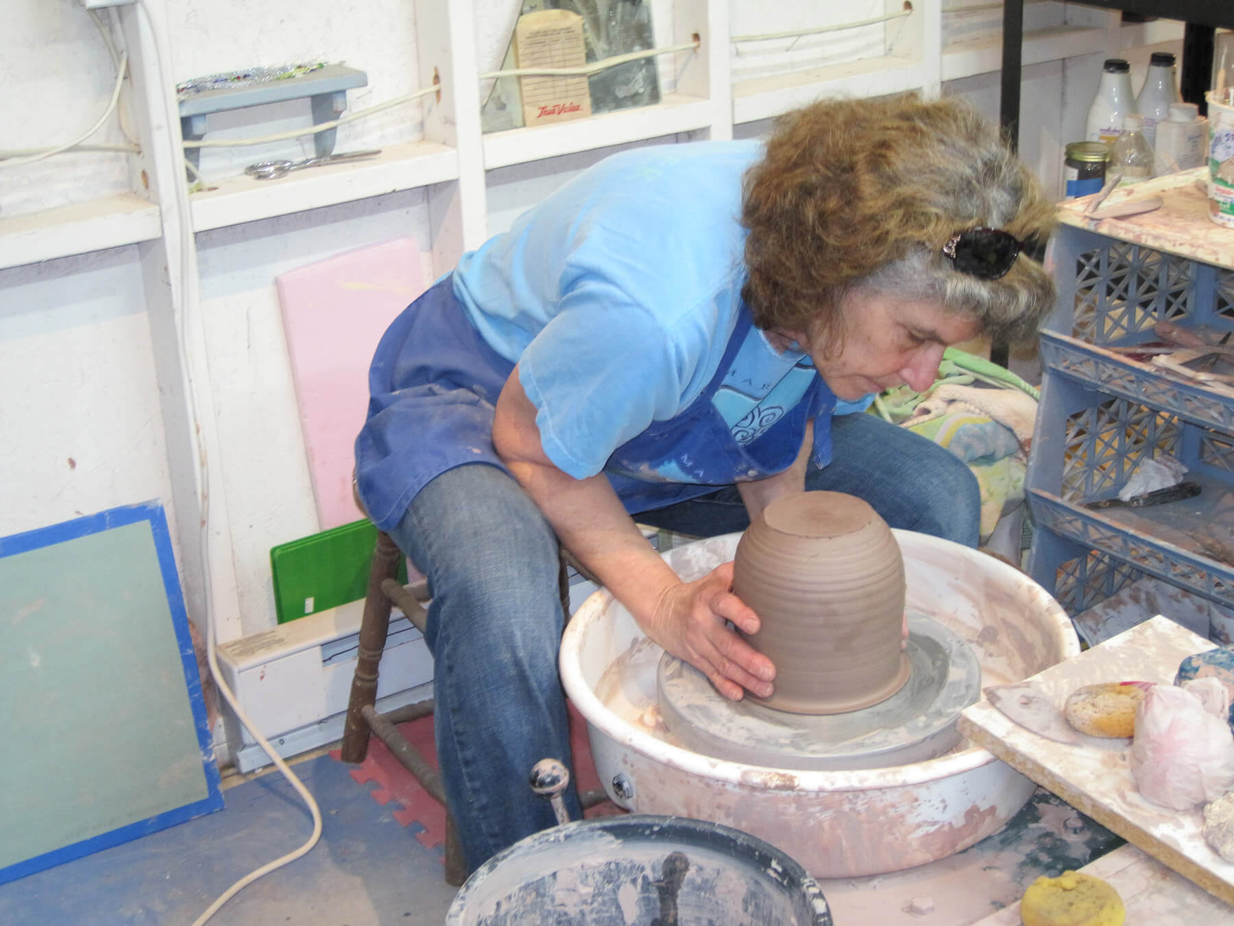a woman sculpting clay on a pottery wheel