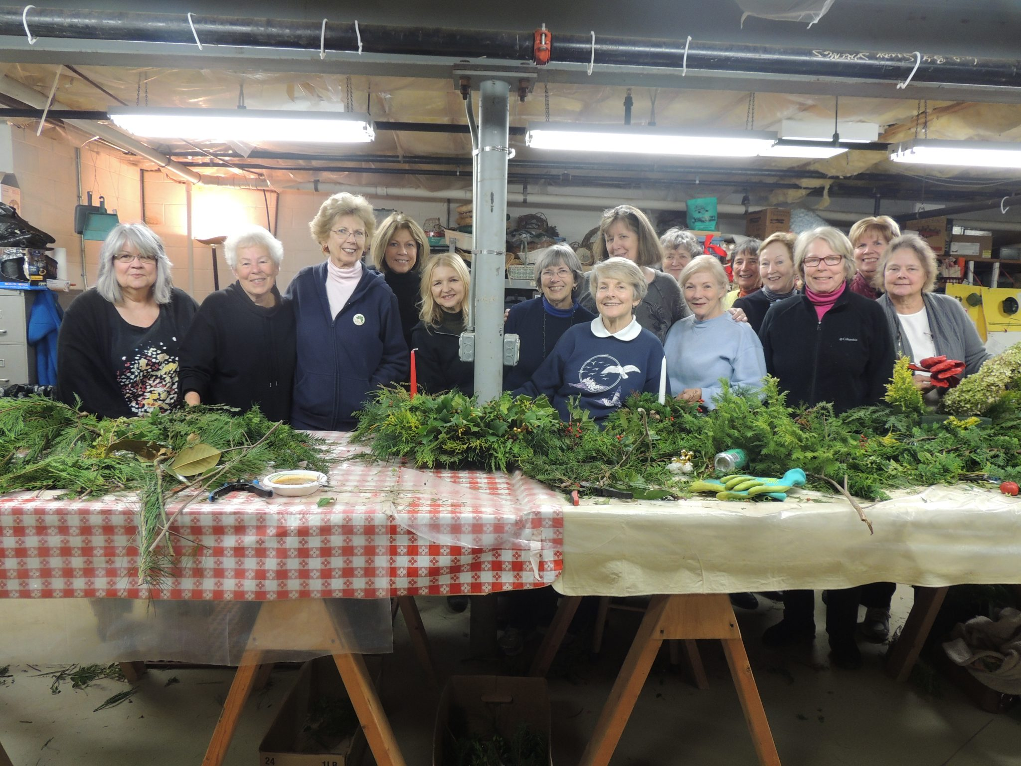 group of women standing behind a table of assorted greens