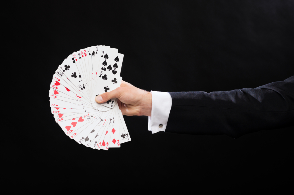 magician hand holding fanned out deck of playing cards