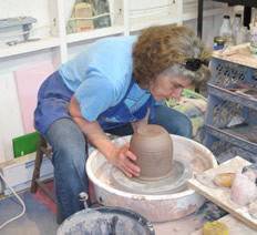 woman sculpting clay on a pottery wheel