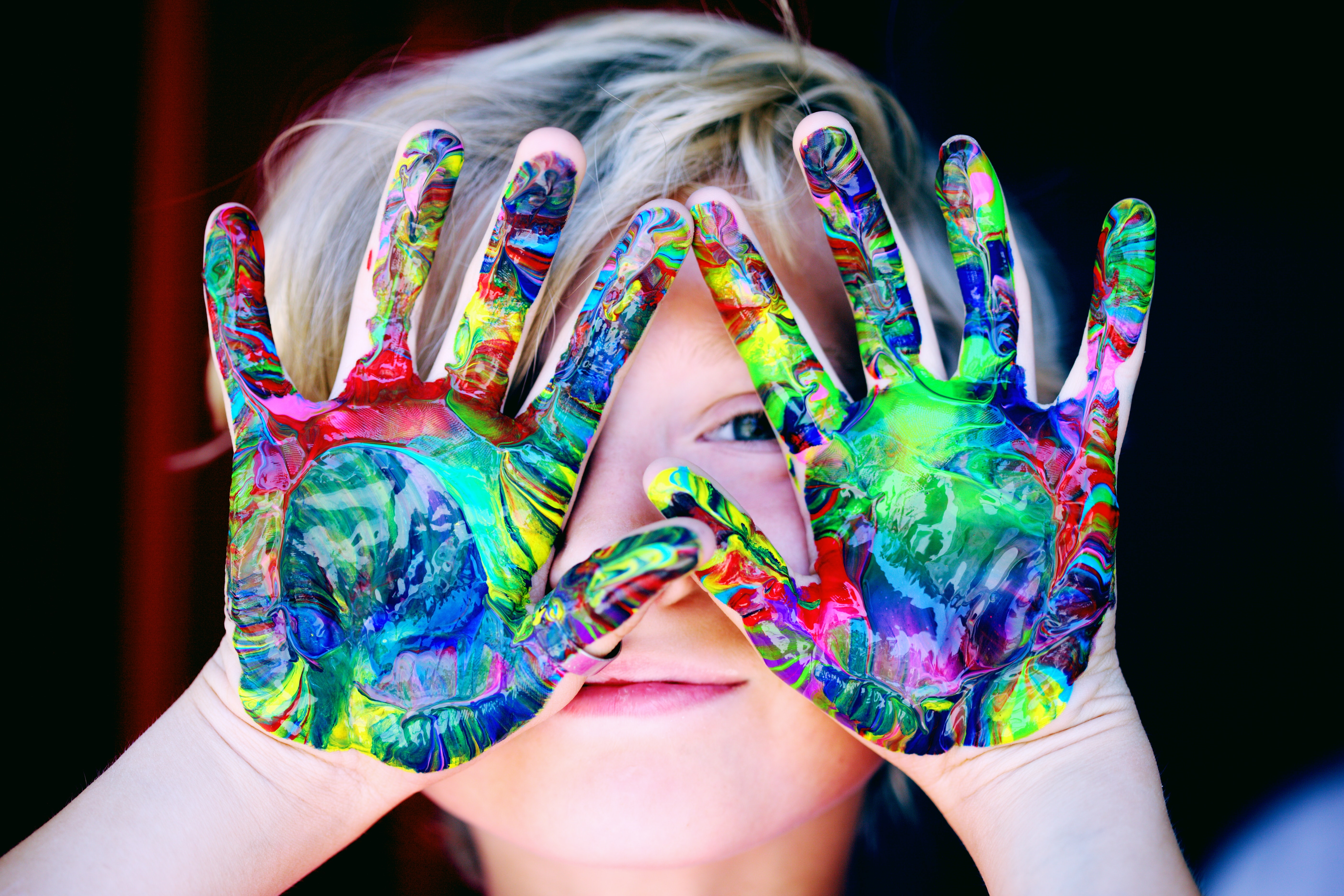child with hands in front of face, palms out, covered in paint