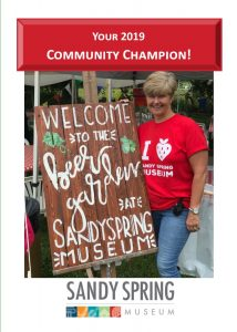 """2019 Community Champion, Glenna Christopher, posing with the """"Welcome to the beer garden at Sandy Spring Museum"""" sign"""