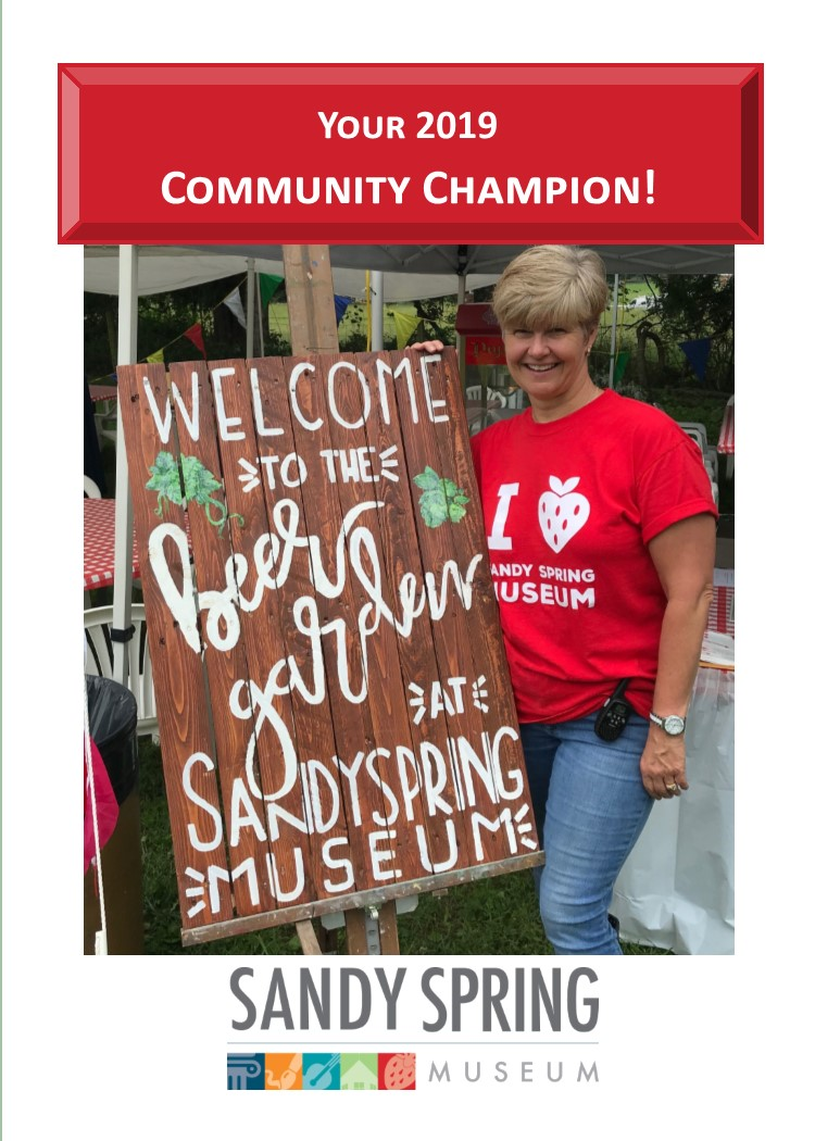 "2019 Community Champion, Glenna Christopher, posing with the ""Welcome to the beer garden at Sandy Spring Museum"" sign"