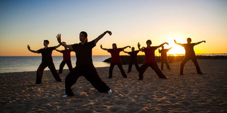 a group of people practicing qi gong on the beach
