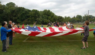 group of people holding open an American flag