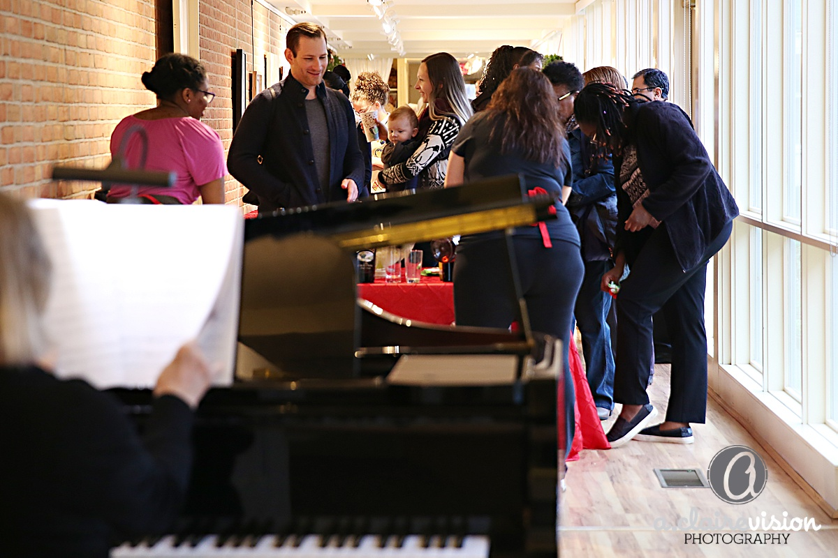 group gathering near the piano at the annual holiday party